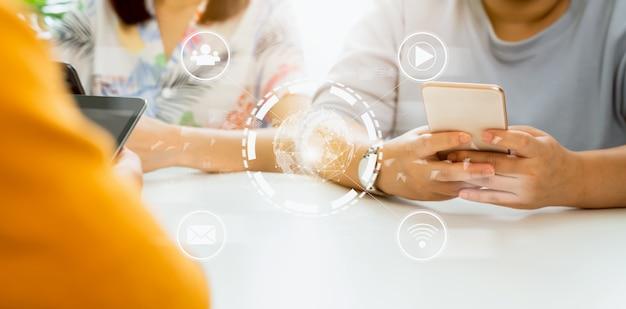 Concept technologie internet et réseautage, groupe d'amis tenant smartphone sur table avec icône média sur affichage numérique.