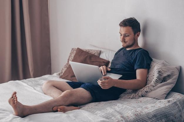 Concept de technologie, de maison et de mode de vie - gros plan d'un homme travaillant avec un ordinateur portable et assis sur un canapé à la maison. jeune homme utilisant son ordinateur portable avec le sourire alors qu'il était assis sur le lit à la maison