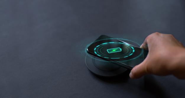 Concept de technologie moderne main qui connecte le téléphone au chargeur sans fil