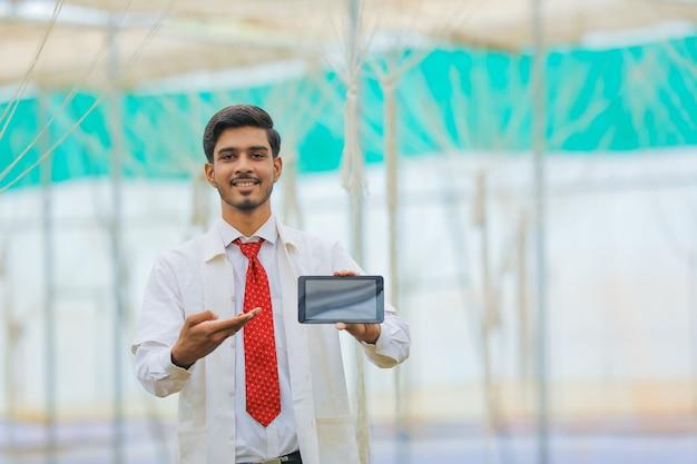 Concept de technologie et de personnes, jeune agronome indien montrant une tablette ou un smartphone à effet de serre