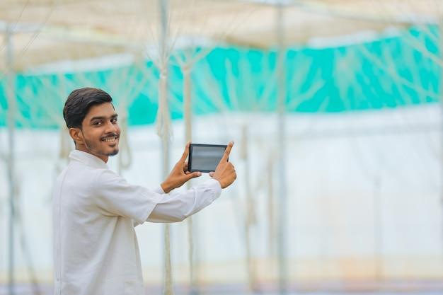 Concept de technologie et de personnes, jeune agronome indien avec tablette à effet de serre