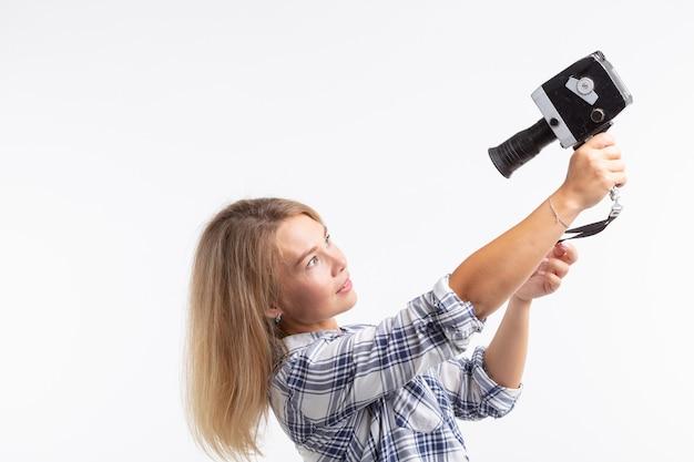 Concept de technologie, photographie et personnes - jolie jeune femme en chemise à carreaux prenant un selfie sur une surface blanche