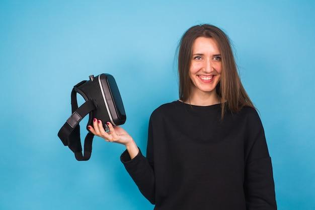 Concept de technologie, réalité virtuelle, divertissement et personnes - heureuse jeune femme avec un casque de réalité virtuelle ou des lunettes 3d.