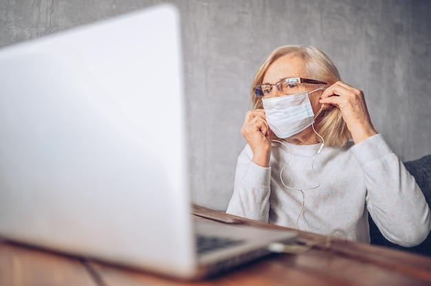 Concept de technologie, de vieillesse et de personnes - femme âgée âgée solitaire triste en masque médical travaillant et effectuant un appel vidéo avec un ordinateur portable à la maison pendant la pandémie de coronavirus covid19. rester à la maison