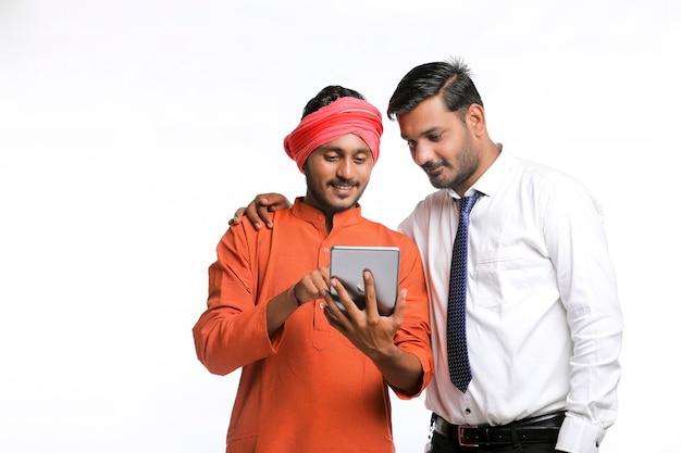 Concept technologique : agent de banque ou employé du gouvernement montrant des détails à l'agriculteur dans une tablette