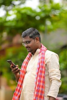 Concept technologique : agriculteur indien utilisant un smartphone