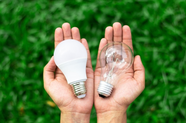 Concept technologique alternatif. mains tenant une ampoule led et une ampoule fluorescente