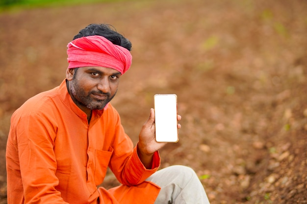 Concept technologique : jeune agriculteur indien montrant un smartphone.