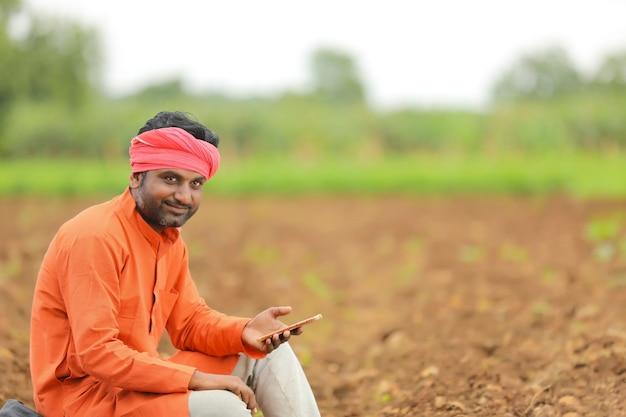 Concept technologique : jeune agriculteur indien utilisant un smartphone sur le terrain