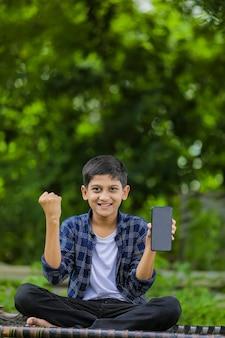 Concept technologique: mignon petit écolier indien tenant un sac et montrant un smartphone