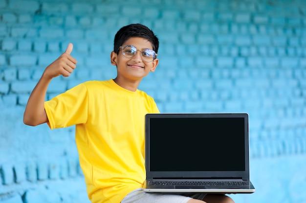 Concept technologique : mignon petit écolier indien utilisant un ordinateur portable et montrant des coups de poing