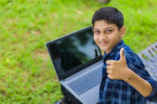 Concept technologique: mignon petit écolier indien utilisant un ordinateur portable