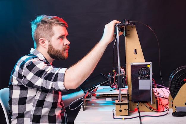 Concept technologique et technique - ingénieur travaillant de nuit dans le laboratoire, il ajuste les composants d'une imprimante 3d.
