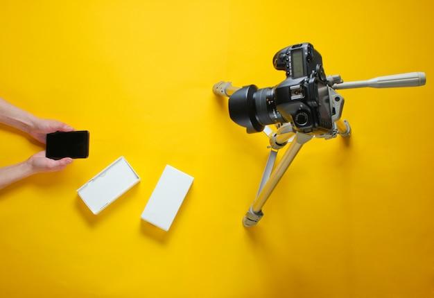 Concept de tehnobloger. mains de femmes déballant le nouveau smartphone avec boîte et blogging avec appareil photo sur trépied. vue de dessus