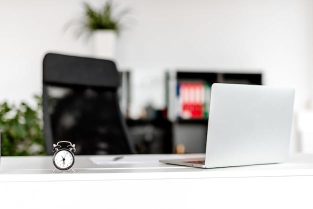 Concept de temps dans le lieu de travail du bureau de la société, réveil et ordinateur portable sur le bureau
