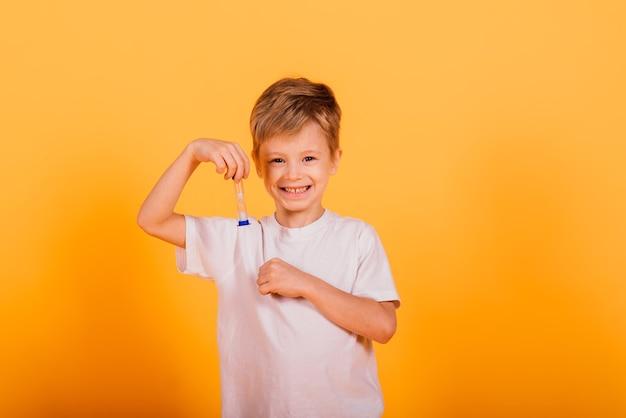 Concept de temps enfant - enfant d'âge préscolaire masculin sérieux appréciant l'apprentissage du temps, tenant un sablier, tourné en studio