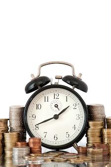 Le concept temps est monétaire: réveil et beaucoup de pièces en euros