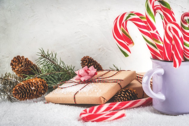 Concept de temps de noël, branches d'arbres de noël, pommes de pin, cadeaux et canne en bonbon de bonbons traditionnels du nouvel an, sur une table en marbre blanc avec de la neige. fond