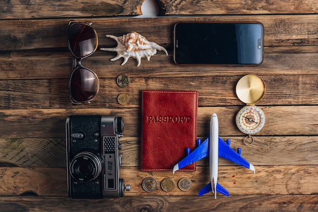 Concept de temps pour voyager, appareil photo, passeport, argent, téléphone avec écran vide, lunettes de soleil et boussole sur fond en bois rustique. planification des vacances. mise à plat, vue de dessus