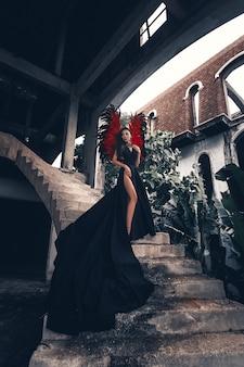 Concept de tentatrice. femme sur un visage passionné joue un jeu de rôle. fille démon sexy en très longue robe noire avec des ailes rouges, diable plein de désir debout dans les escaliers