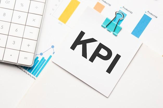 Concept de texte kpi. table de travail de bureau avec calculatrice, graphiques, rapports et le texte budget 2021 sur un petit morceau de papier sur fond multicolore.