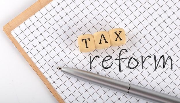 Concept de texte de réforme fiscale écrit sur les blocs de cubes en bois et le cahier