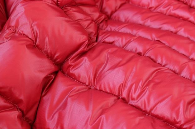 Concept textile et texture - gros plan sur fond de tissu métallique rouge froissé