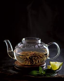 Concept de thé, théière avec thé entouré sur fond de bois, cérémonie du thé, thé vert dans une tasse transparente