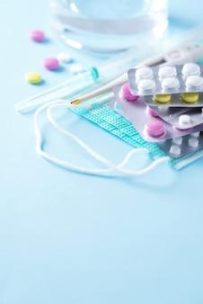 Concept de thérapie, prévention de la grippe virale, attaque virale, pilules contre le rhume, antibiotiques et vitamines, masques médicaux protecteurs sur fond bleu. coronavirus (covid-19. espace copie