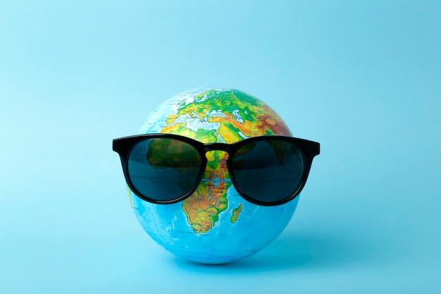 Concept de tourisme, écologie, vacances et globalisme. globe en lunettes de soleil sur une bannière de fond bleu. création minimale