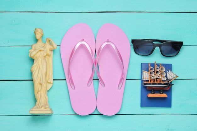 Concept de tourisme. fond de voyageur. voyagez à travers le monde, style plat. accessoires touristiques, souvenirs sur fond de bois bleu.