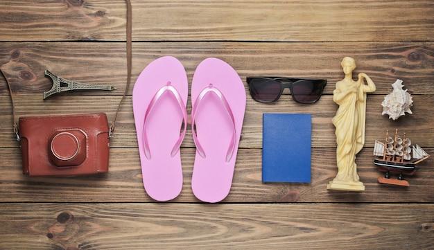 Concept de tourisme. fond de voyageur. voyagez à travers le monde, style plat. accessoires touristiques, souvenirs sur fond en bois.