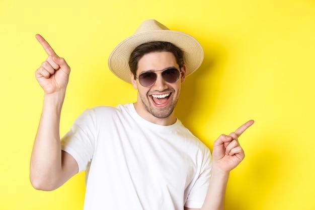 Concept de tourisme et de vacances. gros plan d'un homme profitant de vacances en voyage, dansant et pointant du doigt sur le côté, portant des lunettes de soleil avec un chapeau de paille.