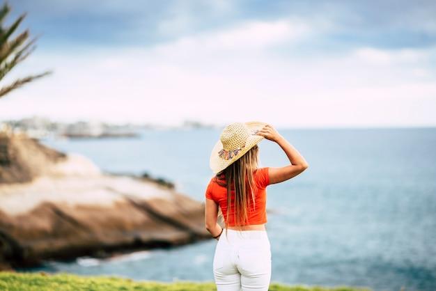 Concept touristique avec une belle touriste vue de dos regardant et profitant de l'océan et du ciel bleus