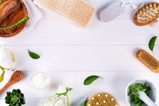 Concept de traitement de spa avec feuilles vertes, produits cosmétiques naturels et brosse de massage sur bois blanc