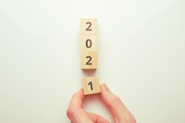 Le concept de la transition vers la nouvelle année 2021. la main tient un bloc de bois.