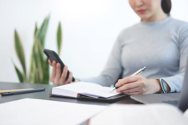 Concept de travail de bureau une femme officier utilisant un téléphone portable pour vérifier l'ordre du jour de la réunion pour demain.
