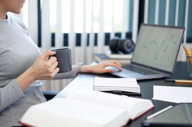 Concept de travail de bureau une femme secrétaire tenant une tasse de café faisant son travail de manière relaxante.