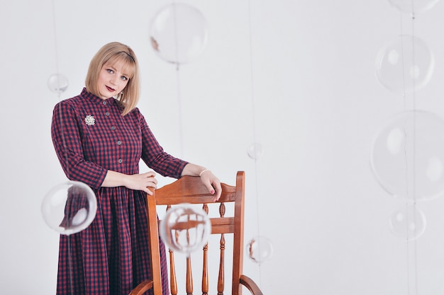 Concept de travail, business model - portrait élégant à la mode d'une femme aux cheveux courts blanc. modèle en robe violette avec broche assis sur une chaise sur fond blanc