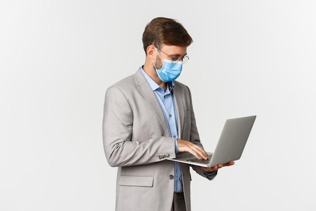 Concept de travail, covid-19 et distanciation sociale. image d'homme d'affaires travaillant dans un masque médical