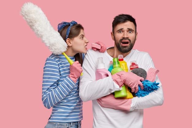 Concept de travail domestique et de relations. une jeune femme irritée et mécontente crie avec colère à son mari paresseux