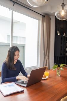 Concept de travail à domicile, une pigiste qui a l'air heureuse tout en travaillant en ligne