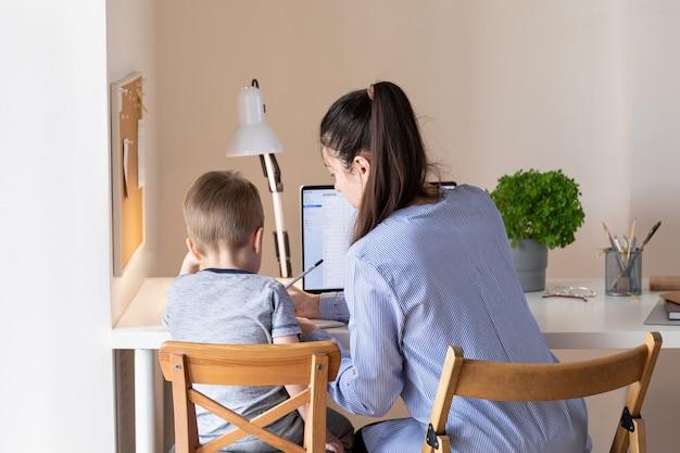 Concept de travail à domicile. travailler à domicile pendant la pandémie de coronavirus covid-19. mère télétravaillant pendant que son enfant joue