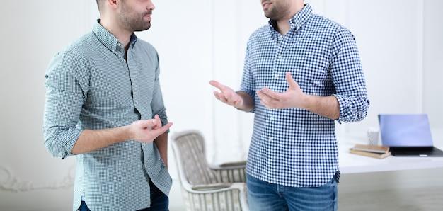 Concept de travail d'équipe commercial. gros plan des mains de deux hommes d'affaires parlant au bureau. ordinateur portable, café et ordinateur portable sur tableau blanc.