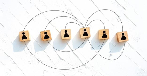 Concept de travail d'équipe et de communication, blocs de bois rectangulaires sur une table en bois blanche.
