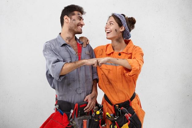Concept de travail d'équipe et de coopération. heureux les ouvriers de maintenance positifs se tiennent la main