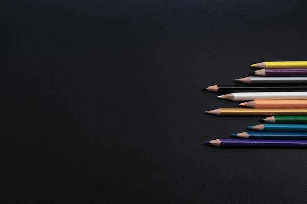 Concept de travail d'équipe. groupe de crayon de couleur sur fond noir