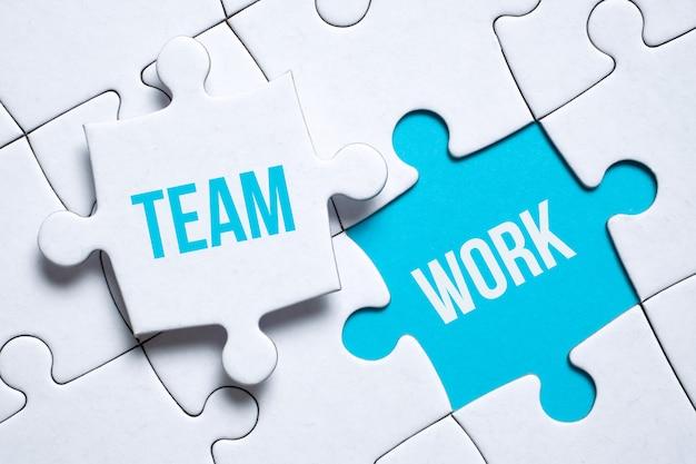 Concept de travail d'équipe. une pièce du puzzle avec l'inscription tient les doigts d'un homme à côté d'un autre sur une surface bleue