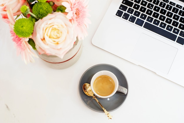 Concept de travail féminin dans un style plat laï avec ordinateur portable, café, fleurs. vue de dessus, brillant, rose et or