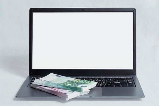 Concept de travail et d'investissement en ligne. maquette d'ordinateur portable avec un paquet de factures en euros sur fond blanc.